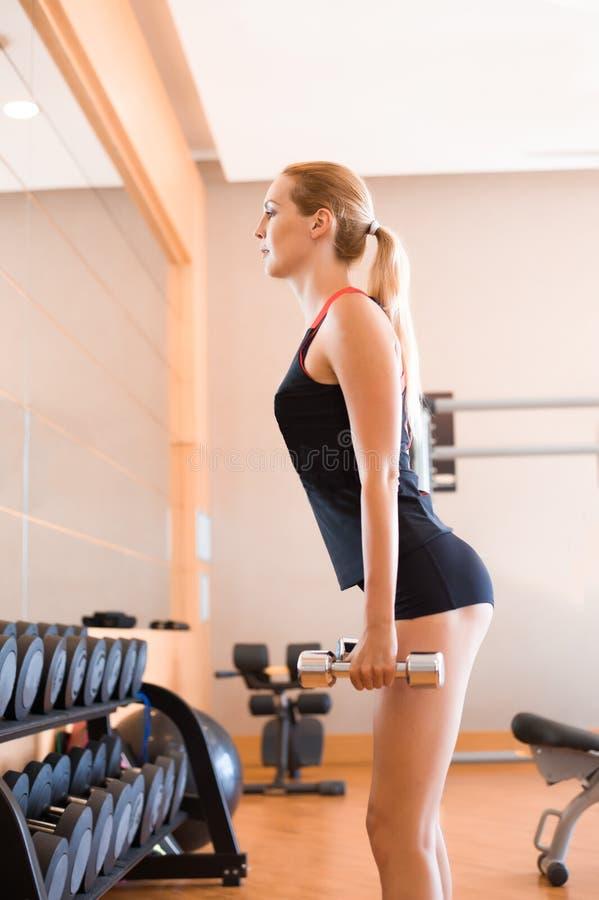短的参与在健身房的健身运动服和一件黑无袖的球衣的年轻美女 免版税库存图片