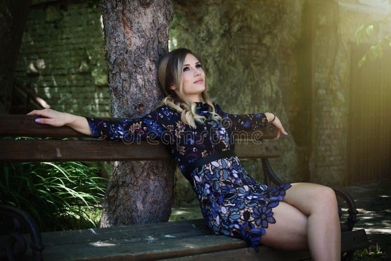 短的庄重装束的美丽的女孩坐长木凳为 免版税库存照片