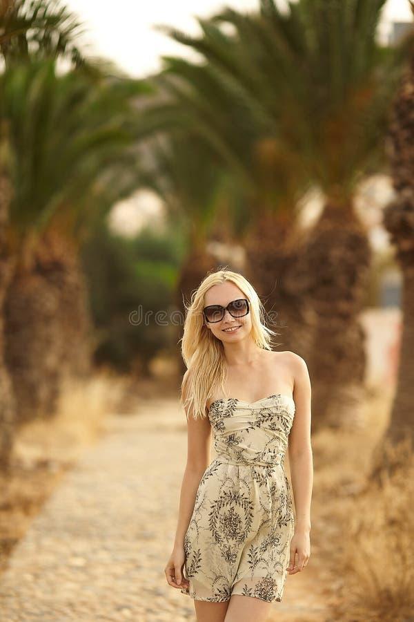 短的摆在棕榈树中的礼服和太阳镜的美丽的时兴的金发碧眼的女人 免版税库存图片