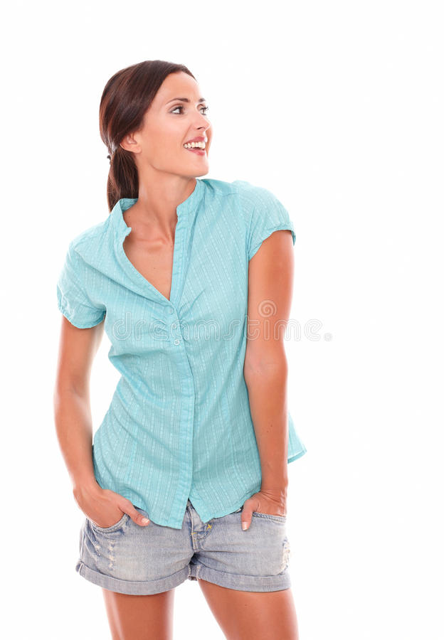 短的牛仔裤的愉快的妇女朝她的左边看 图库摄影
