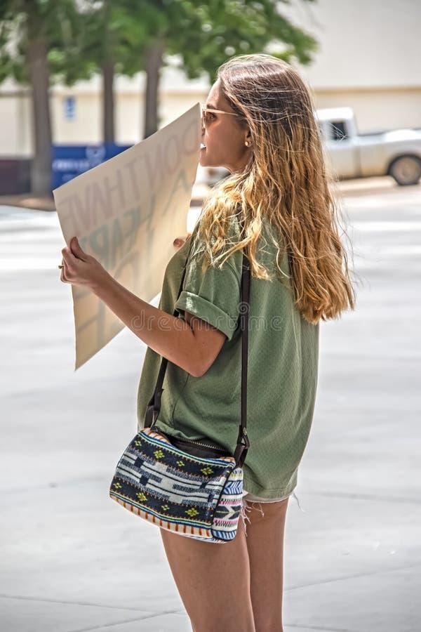 短的短裤和太阳镜的可爱的被晒黑的妇女有长的深色的头发和逗人喜爱的钱包的待命 库存图片