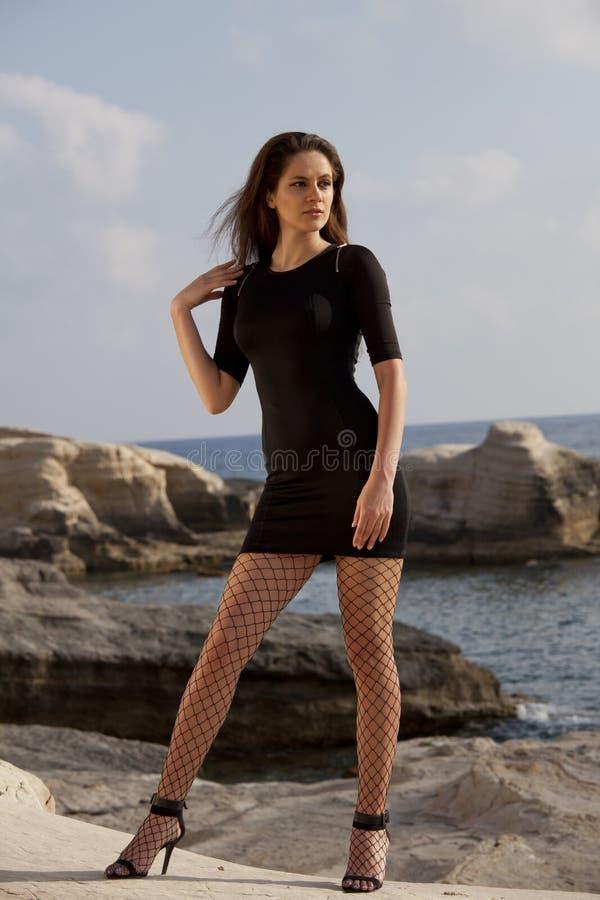 短的礼服的妇女在海滩 免版税库存图片