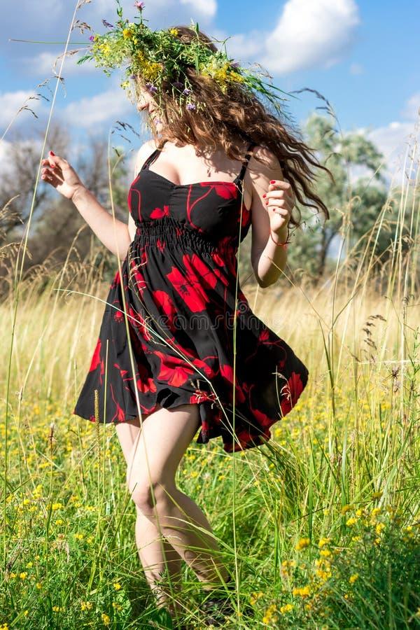 短的礼服的愉快的女孩有一五颜六色的garlang的由野花制成在她的头在草甸跳舞并且笑 免版税图库摄影