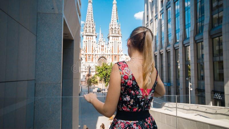 短的礼服的走在有现代和老大厦的老城市的美丽的少女画象  女性游人 免版税库存照片
