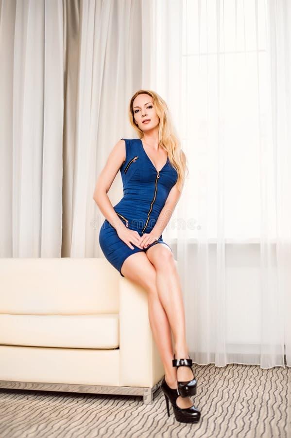 短的蓝色礼服的妇女在沙发在绝尘室 库存照片