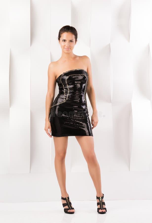 短的黑礼服的年轻美丽的妇女 寻找党 免版税库存照片