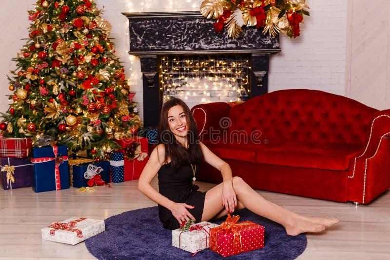 短的黑礼服的深色的妇女坐地毯在圣诞树附近 笑的妇女年轻人 美丽的女性 图库摄影
