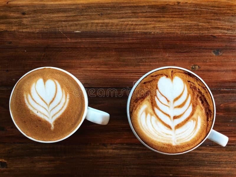 短笛拿铁艺术咖啡和热奶咖啡咖啡在白色杯子 免版税库存图片