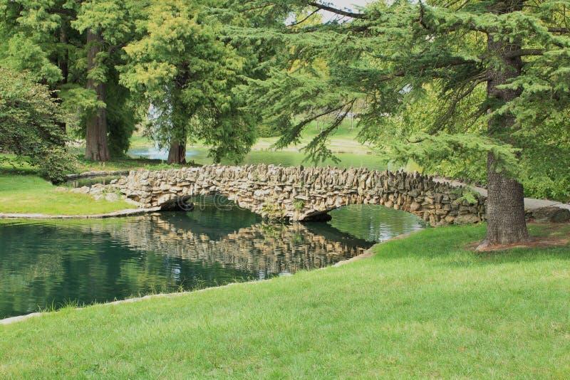 石人行桥横穿池塘在春天树丛公墓,辛辛那提,俄亥俄 免版税图库摄影