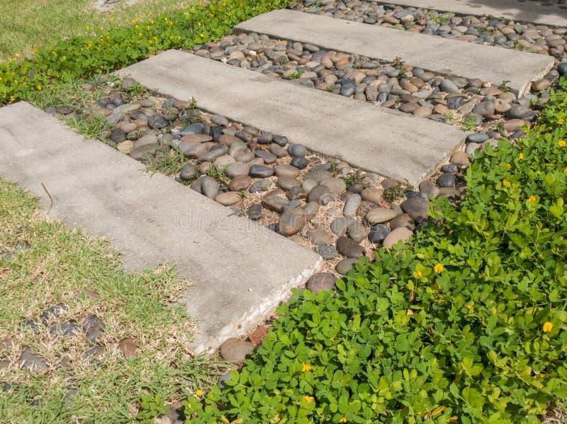 石块步行方式在有绿草和岩石的庭院里 免版税库存图片