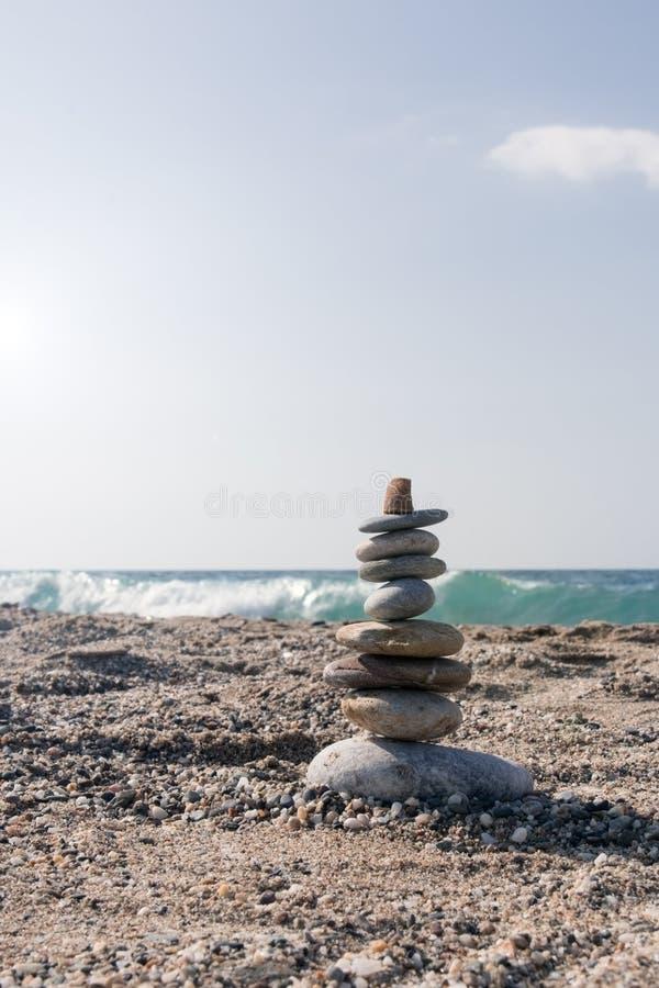 石头九个片断在平衡的在搅动的海边 库存照片