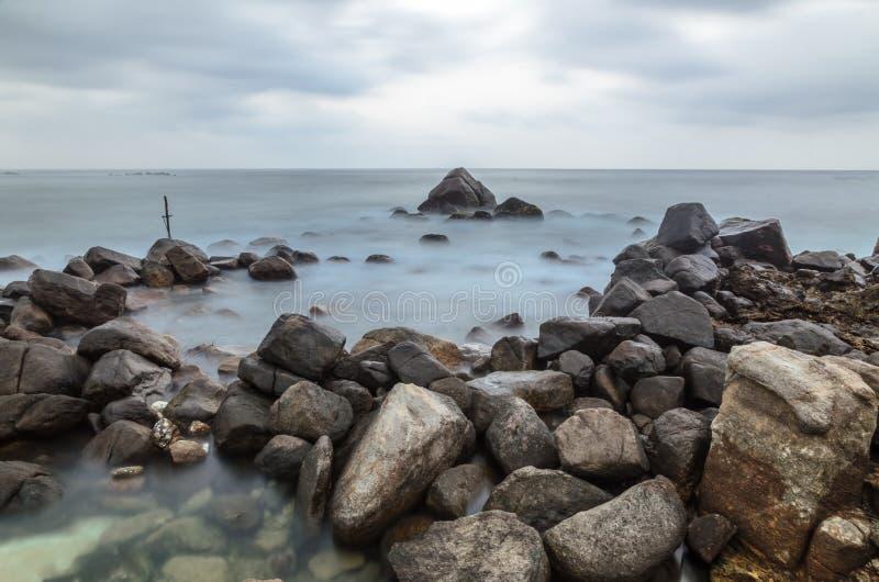 石头和一个十字架在海滨 免版税库存图片