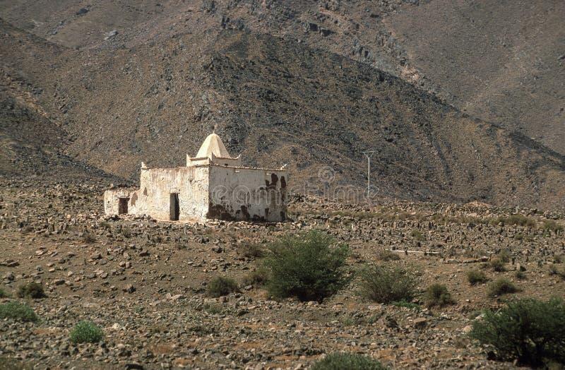 石头和灌木贫瘠风景的小清真寺包围的,摩洛哥 免版税库存照片