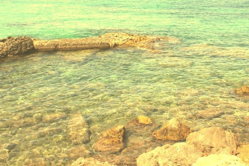 石头和透明的大海 免版税库存照片