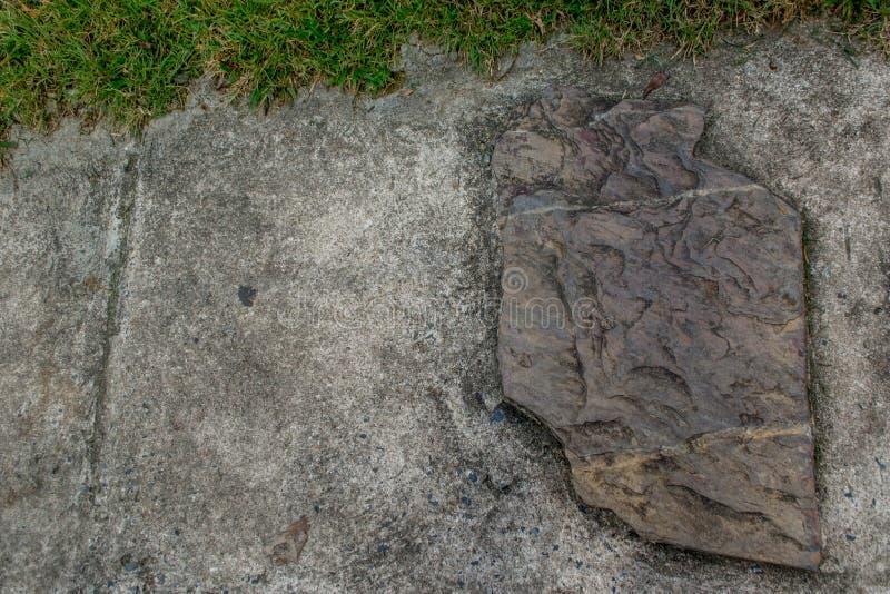 石头在水泥地板和草被放置 免版税库存图片