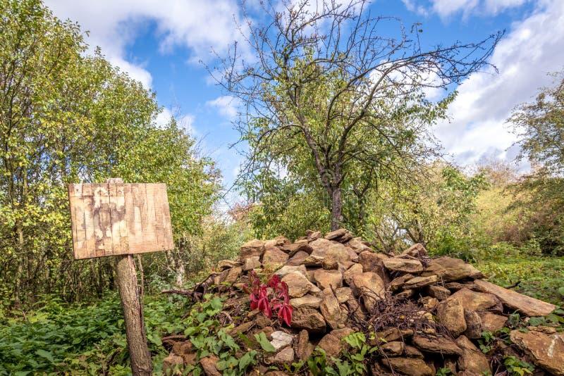石头大垃圾填埋与一个木标志的 免版税图库摄影