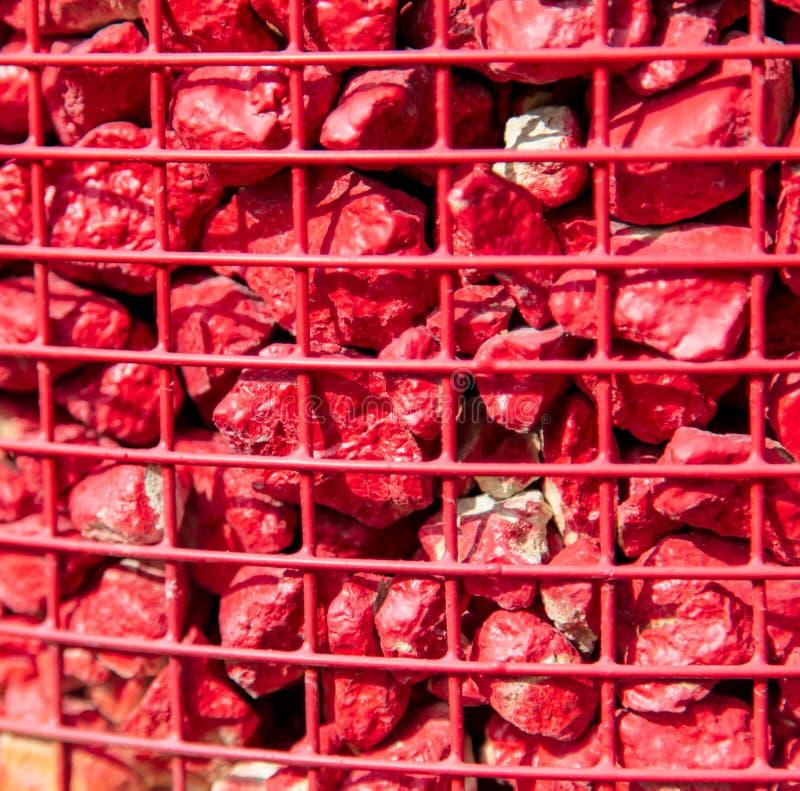 石头绘与在金属栅格的红色油漆作为背景 库存图片