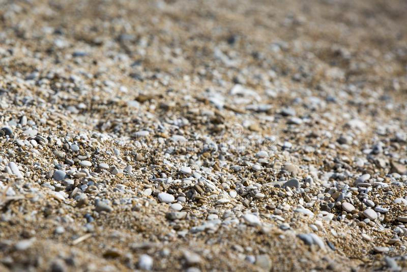 石头背景在岸的 关闭在距离的模糊的日落光 免版税库存图片