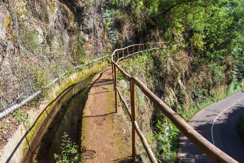 石头铺成的勒瓦达在山村上方的一条路上,边上铺着木栏杆 库存图片
