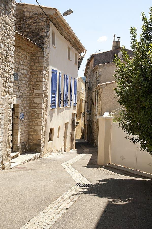石房子街道有蓝色快门的 免版税库存图片