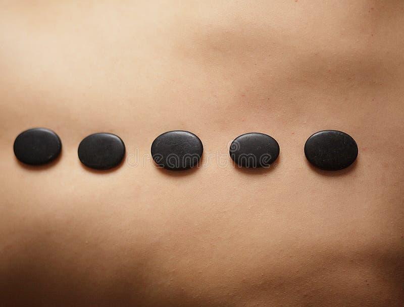 石按摩 得到温泉在温泉沙龙的美丽的妇女热的石头按摩 免版税库存图片