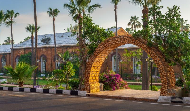 石显露皇家植物托儿所的砖橙色曲拱在有树和棕榈的,亚历山大,埃及Montazah公园 库存照片