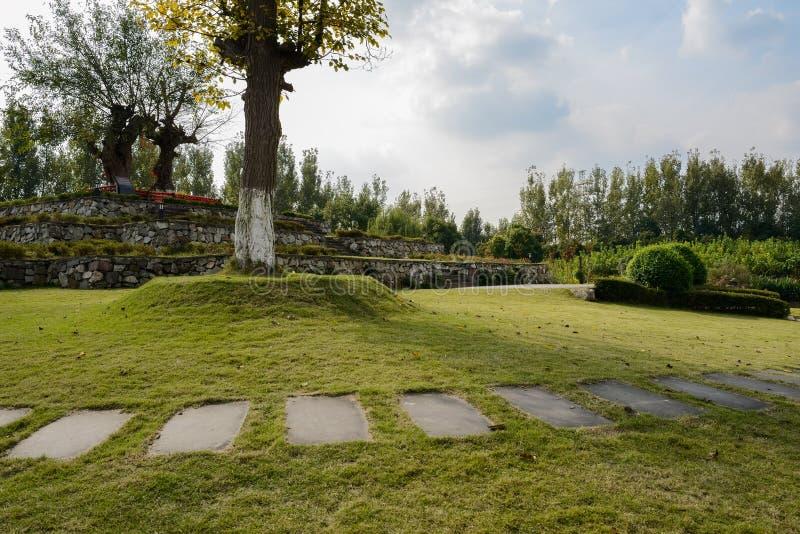 石板被铺的道路在多云下午的草坪 免版税库存图片