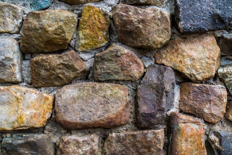 石样式用不同的大小和颜色,墙壁由猎物岩石做成和水泥,现代庭院建筑学 库存图片
