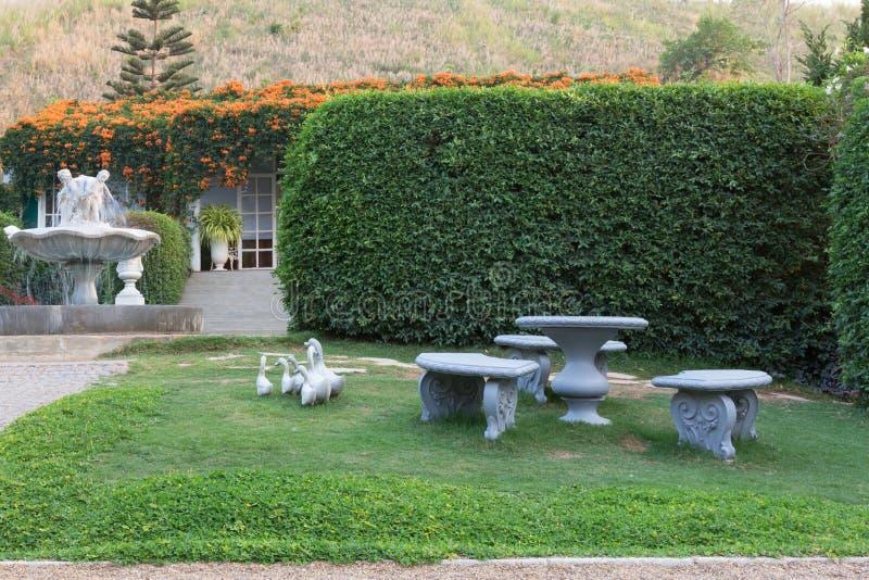石桌和椅子在庭院里 免版税库存照片