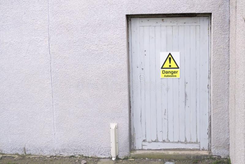 石棉在门的危险标志在老大厦建造场所  库存图片