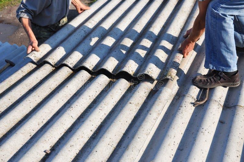 石棉屋顶建筑 安装石棉屋顶板料的盖屋顶的人 库存图片