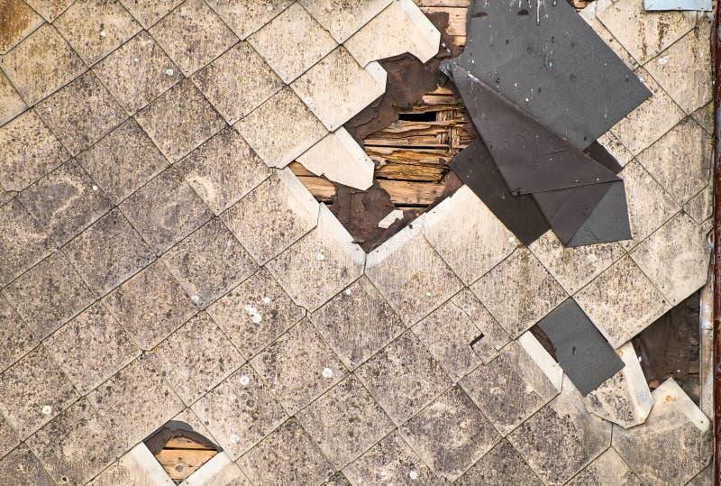 石棉木瓦老损坏的屋顶要求修理的 肮脏的射线和被撕毁的防水屋面材料 免版税库存图片