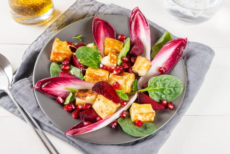 石榴、甜菜根、红色苦苣生茯、菠菜、薄菏和halloumi沙拉 库存图片