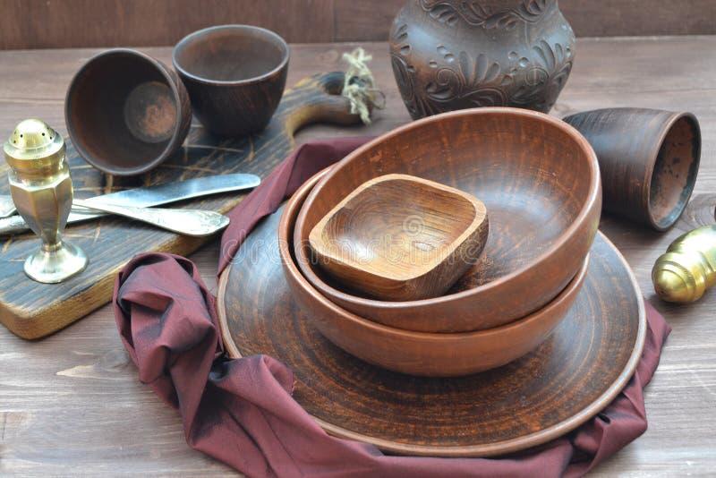石榴汁糖浆颜色空的餐馆碗筷和餐巾  土气木棕色背景 免版税图库摄影
