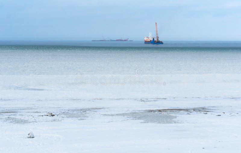 石油平台在天际的冬天海,冰烂泥在海 免版税库存图片