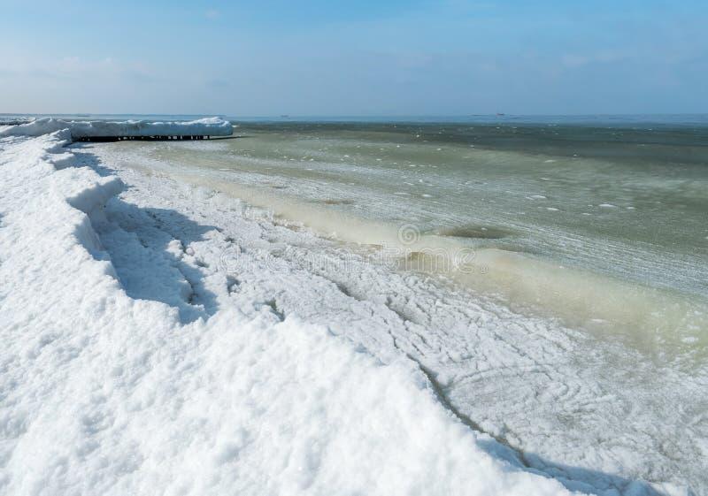 石油平台在天际的冬天海,冰烂泥在海 免版税库存照片