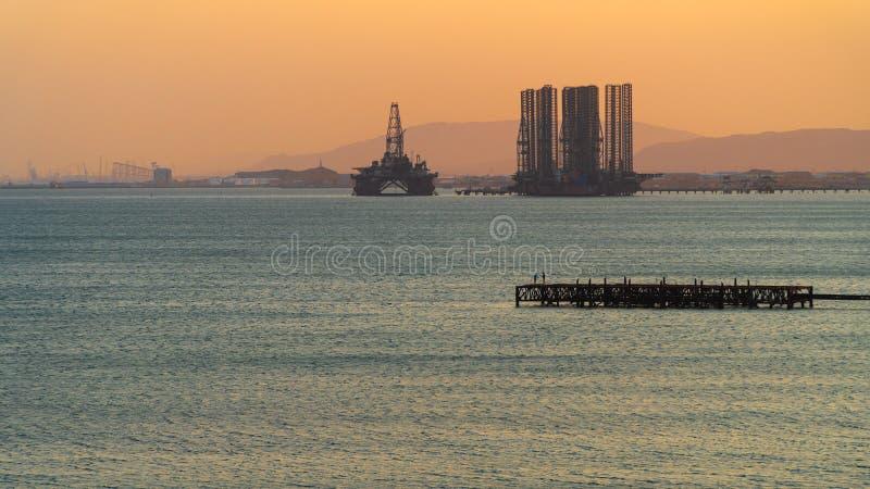 石油平台在日落的海 免版税库存照片