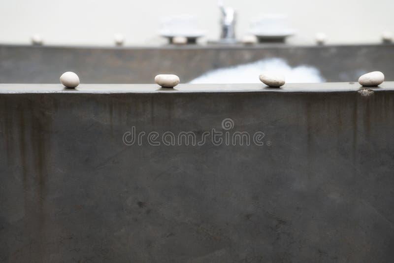 石浴充满面汤和泡沫 在浴的边缘是被计划的小白色小卵石 图库摄影