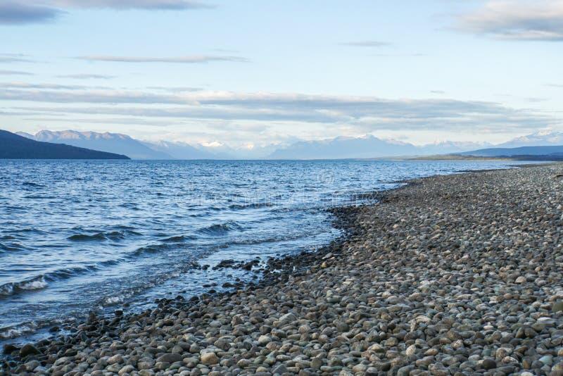 石海滩在日落新西兰的蓝色湖边 免版税库存照片
