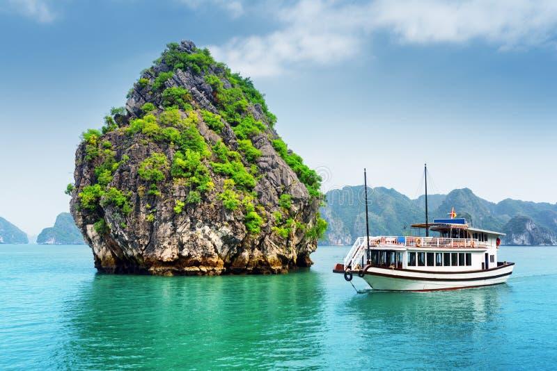 石灰岩地区常见的地形小岛和游船美丽的景色在下龙湾 免版税图库摄影