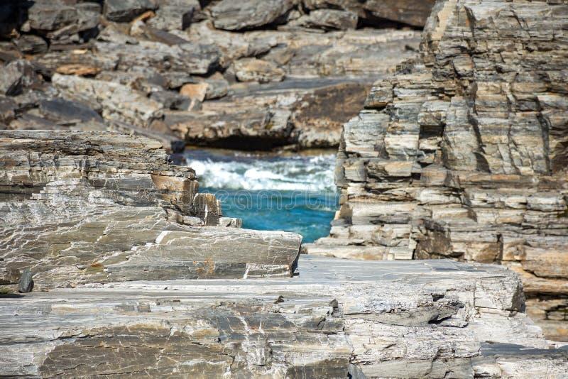 石灰石不同的层数晃动围拢在阿比斯库国家公园峡谷的冰河河急流 免版税图库摄影