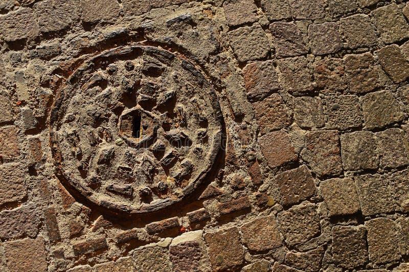 石织地不很细路面和老肮脏的出入孔与金属盖子 库存图片