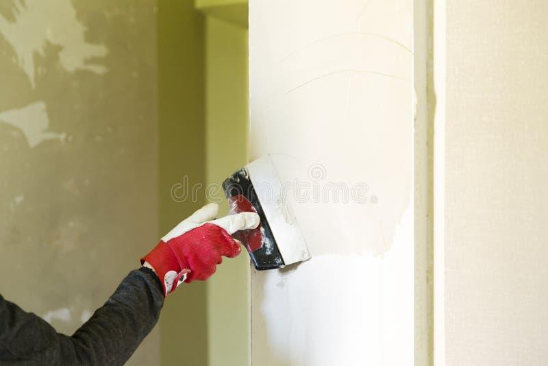 石膏工住所改善有运转在公寓墙壁装填的油灰刀的杂物工工作者 家庭整修概念 免版税图库摄影