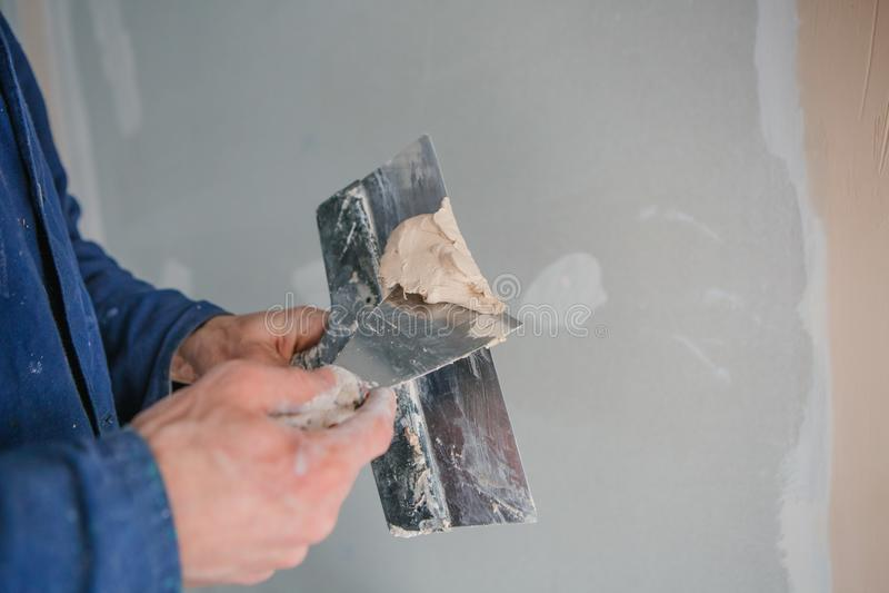 石膏工工作者工具油灰修平刀的手 免版税图库摄影