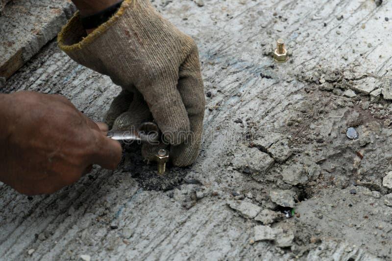 石膏工拉紧在水泥地板上的坚果 库存图片