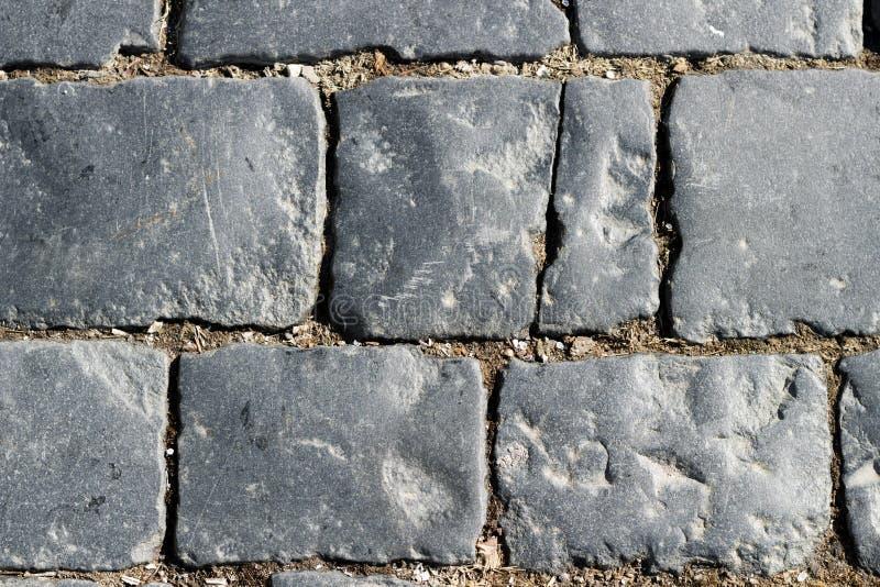 石路面纹理,花岗岩铺有鹅卵石的路面背景,修补了石路规则形状,抽象背景 免版税图库摄影
