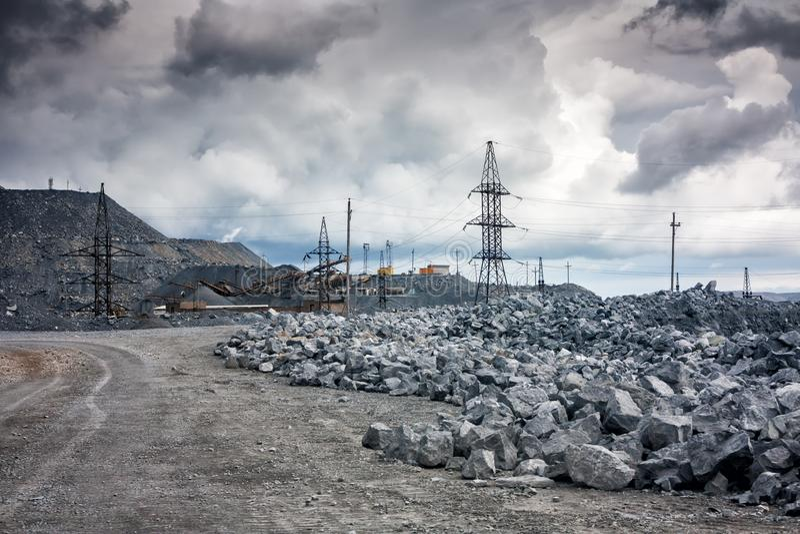 石转储,输电线和击碎机器在一件猎物在多云天气 图库摄影