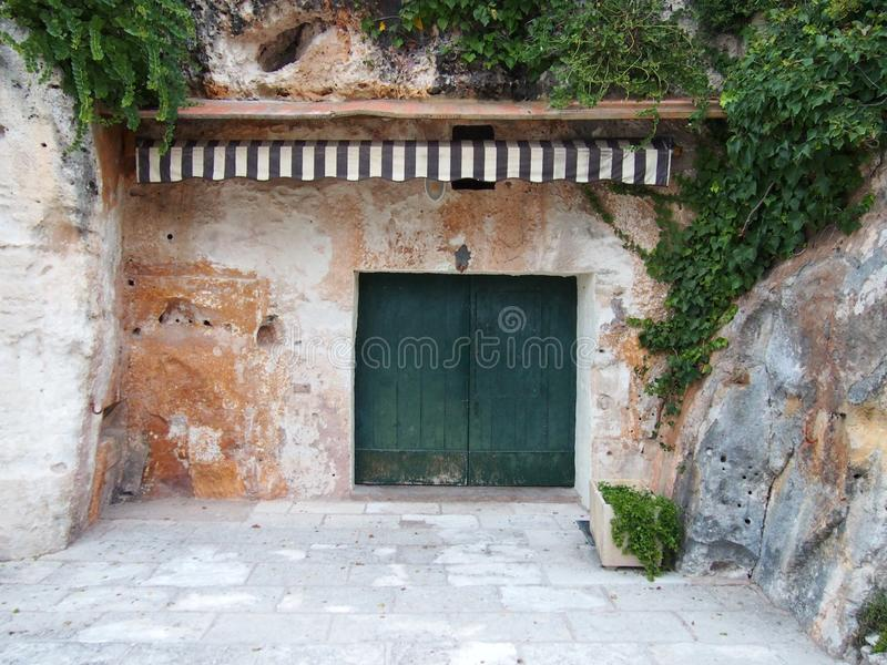 石避难所被雕刻在与绿色植被木门和一个镶边遮篷的峭壁外面 库存照片