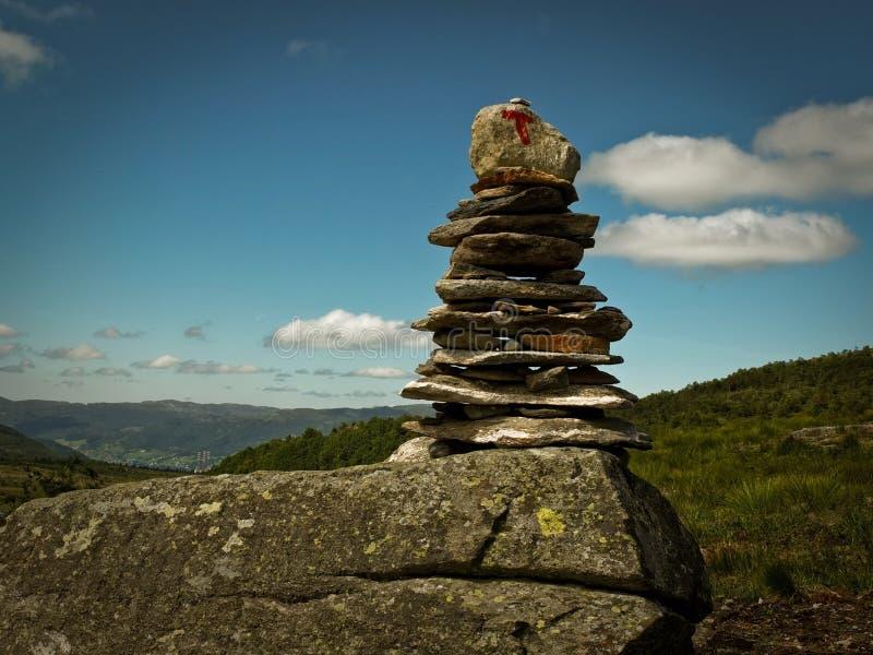 石金字塔喜欢在供徒步旅行的小道的证明标志在绿色山谷的背景 库存照片