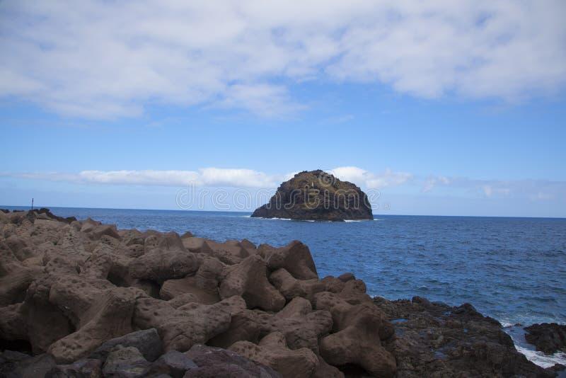 石头在海岛附近的海 免版税库存图片
